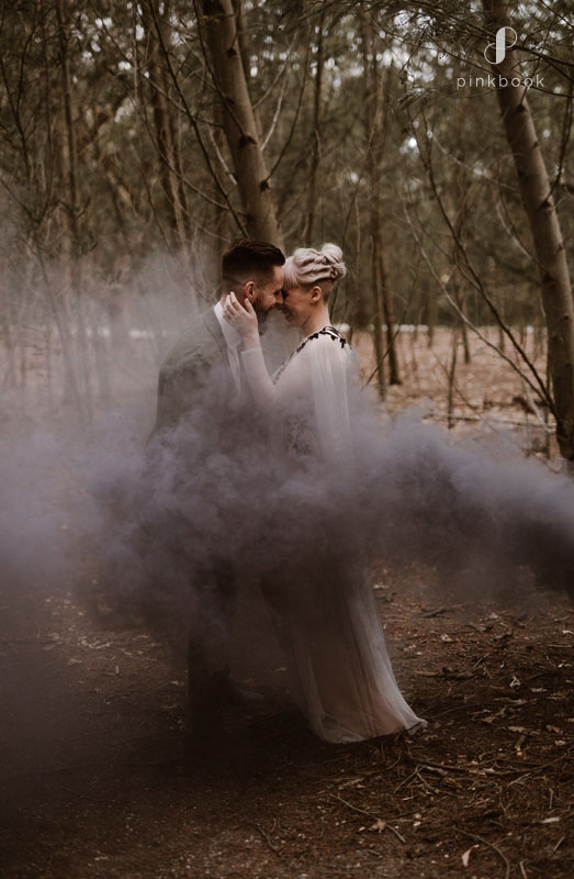 Bride and groom kissing in the smoke