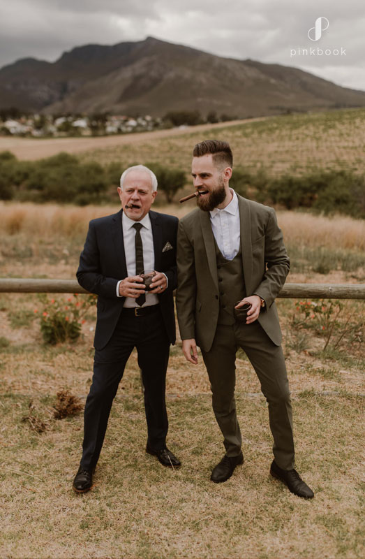 Groom and his father smoking a cigar