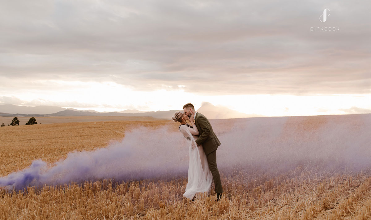 Newlyweds kissing with purple smoke in the background.