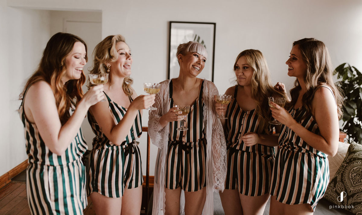 Bride and her Bridesmaids drinking champagne laughing
